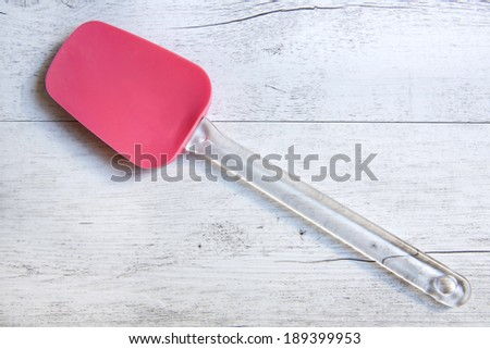 Silicone spoon isolated on wooden background - stock photo