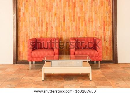 Silk sofa and brown brick wall on stone floor - stock photo