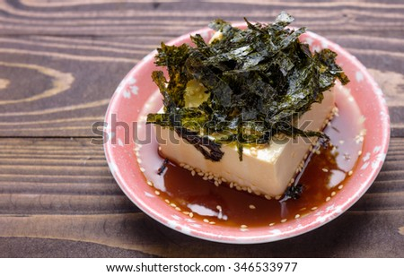 Silken tofu sesame oil decorate, cold bean curd, soybean with seaweed in bowl on wooden background - stock photo