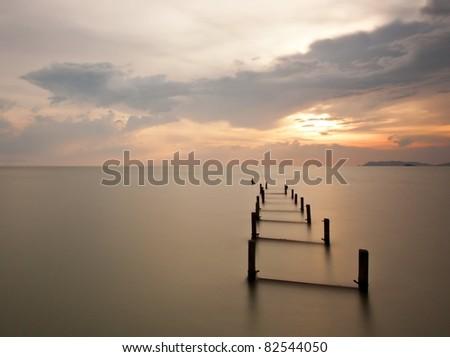 Silky sunset with lonely broken bridge - stock photo