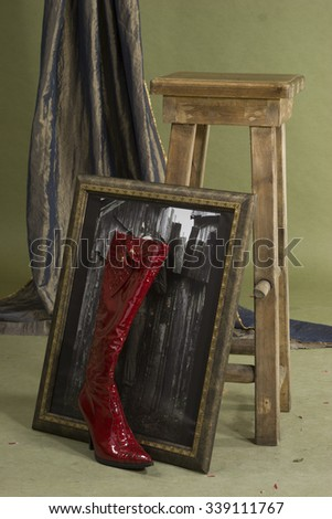 Sill life of boot picture and stool in studio room - stock photo