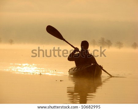 Sillouette of man kayaking on lake at sunrise - stock photo