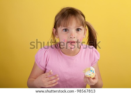 Silly blonde girl eating a cupcake on a yellow background - stock photo
