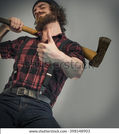 Silly hipster lumberjack gives thumbs up sign while holding axe - stock photo