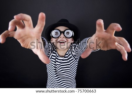 Silly little boy in black hat and striped vest with play eyeball glasses. I'm coming for you - stock photo