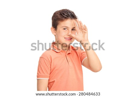 Silly little boy making a childish hand gesture and looking at the camera isolated on white background  - stock photo