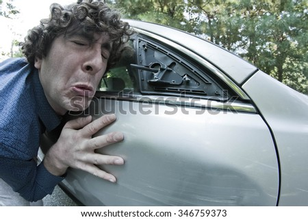 Silly man makes angry annoyed facial expression about dame to his car - stock photo