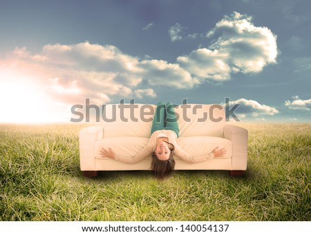 Silly woman sitting upside down on couch in sunny field in countryside - stock photo