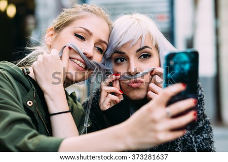 Silly Young women best friends taking a selfie - stock photo