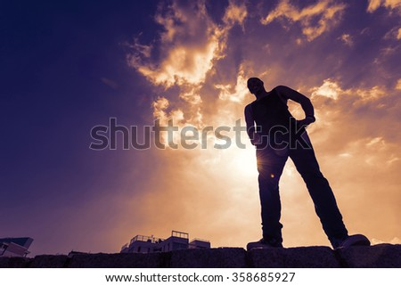 Silouette full body portrait of parkour man standing against dramatic purple sky. Filtered image with modified colors. - stock photo