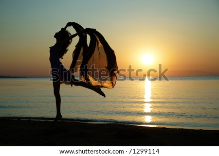Silouette of the nifty woman dancing at the sea during sunset. Natural light and darkness. Artistic colors added - stock photo
