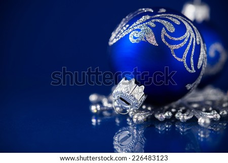 Silver and blue christmas ornaments on dark blue background with space for text - stock photo