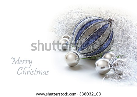 silver and blue xmas baubles as decoration on a white background, copy space with sample text Merry Cristmas - stock photo