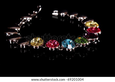 silver and diamonds bracelet with color  stones on black background - stock photo