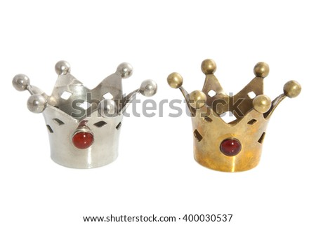 Silver and golden crowns with gems isolated over white - stock photo