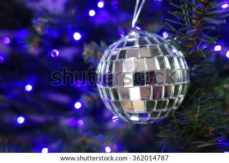 Silver ball hanging on a Christmas tree with blue lights in the background - stock photo