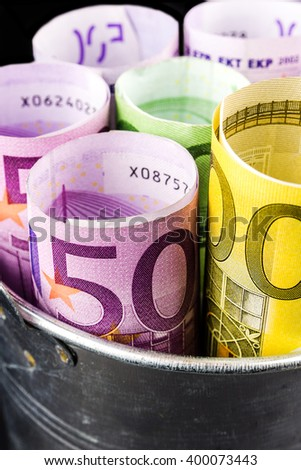 silver basket full of big euro banknotes on black background - stock photo