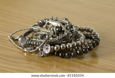 silver bracelets isolated on a wooden background - stock photo