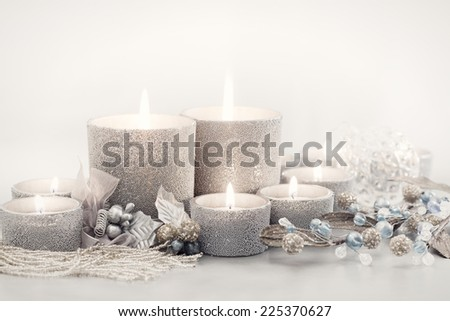 Silver candles & tealights with Christmas ornaments on gray background. Room for copy space.  - stock photo