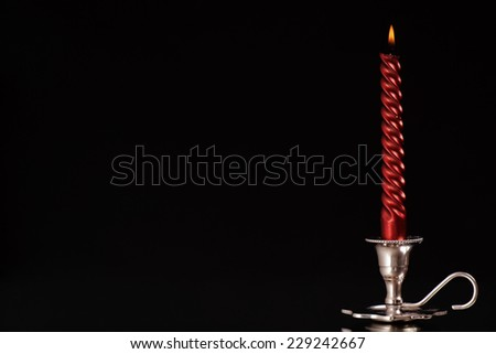 silver candlestick with one burning red candle in front of black background/silver candlestick - stock photo