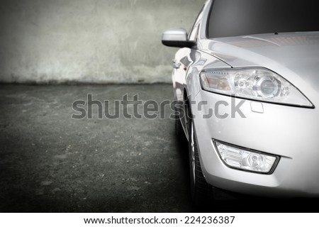 silver car without a trade brand in dark garage  - stock photo