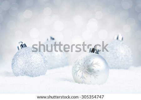 Silver Christmas baubles on snow with defocused silver and white lights in the background. Shallow depth of field. - stock photo