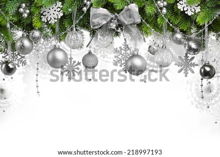 Silver Christmas ornaments hanging on fir tree - stock photo