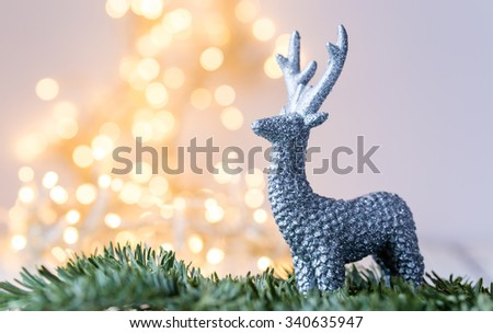 silver deer in front of blurred christmas lightening - stock photo