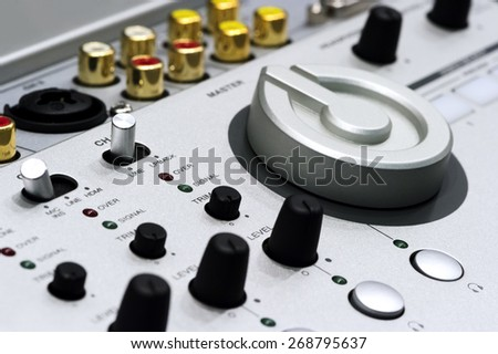 Silver DJ mixer controller with buttons, switches, faders, knobs, other toggle items, plugs and connectors, selective focus - stock photo