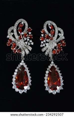 Silver earrings with jewels on the black - stock photo