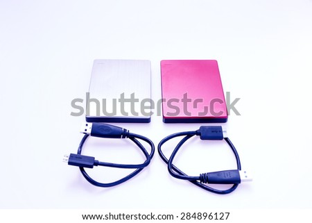 Silver external hard disk and red external hard disk with their USB connectors on white. - stock photo