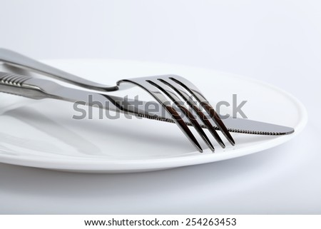 Silver fork and knife on the plate - stock photo