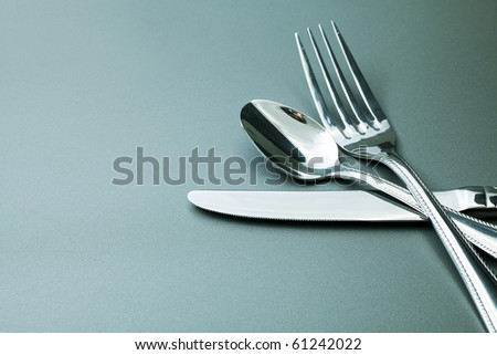 Silver fork, knife and spoon  over grey background. - stock photo