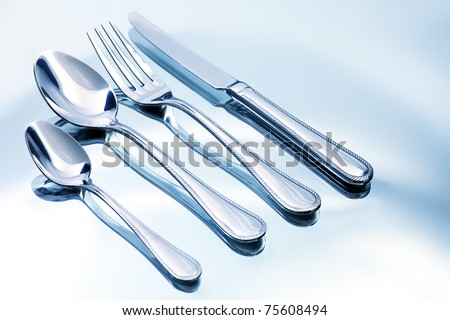 Silver fork, knife and spoons on a white plate. - stock photo