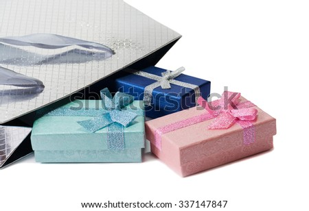 Silver gift bag and blue and pink gift boxes isolated on white. Selective focus - stock photo