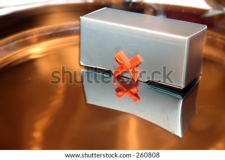 Silver gift box with orange ribbon on a golden plate - stock photo