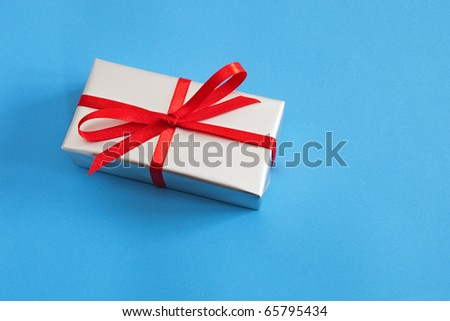 silver gift box with red ribbon on the blue background - stock photo