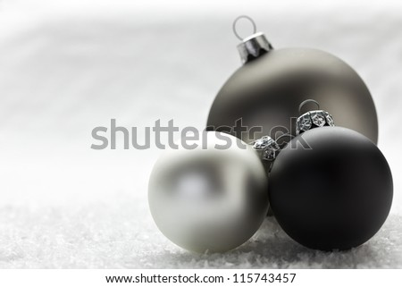 silver, gray and black christmas baubles on artificial snow - stock photo