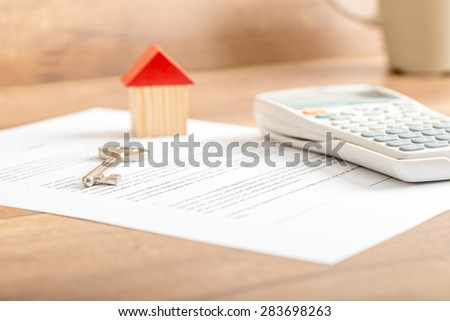 Silver house key lying on a contract for house sale, lease, insurance or mortgage in a real estate concept, viewed low angle with focus to the tip. - stock photo