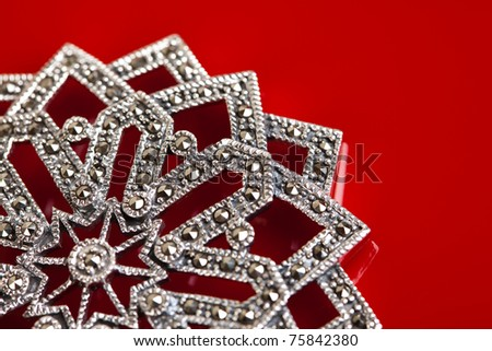 Silver jewelery over red background - stock photo