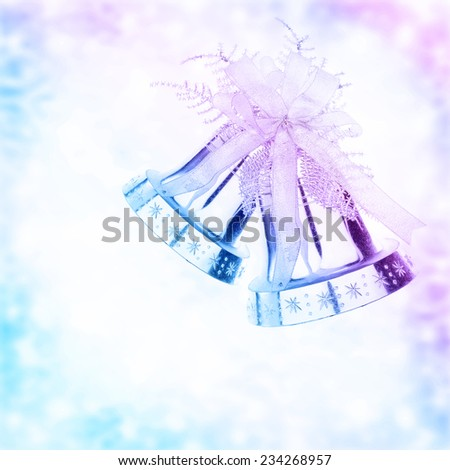 Silver jingle bell border, Christmas tree ornament and holiday decoration isolated on blue and purple blurry background - stock photo