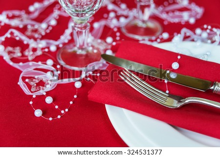 Silver knife and fork lie on the red linen napkin, as well as wineglass, which is located on a table covered with a red tablecloth, with space for text - stock photo