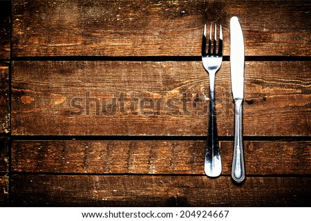 Silver Knife and fork over wooden table with copy space. Diet Food concept. - stock photo