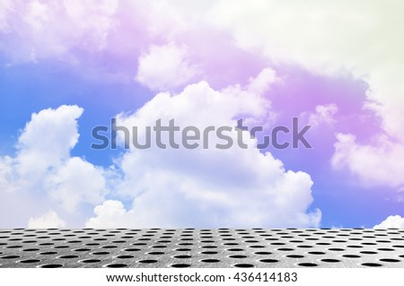 silver metal floor with round hole and multicolored sky background - stock photo