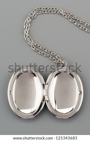 Silver necklace with pendant shot on gray background - stock photo
