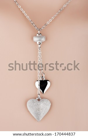 Silver necklace with two heart pendants on a mannequin - stock photo