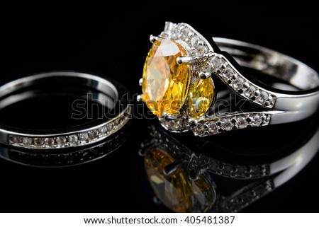 Silver or white gold rings with yellow gems and diamonds on black glass background - stock photo