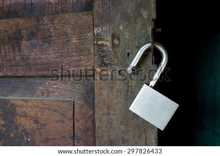 Silver padlock hanging on old wooden doors - stock photo