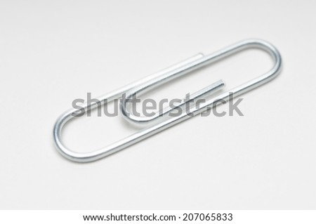 Silver paper clip on white background - stock photo