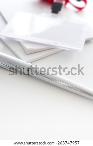 Silver pen and security or ID card with red strap. Shallow depth of field. - stock photo